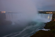 A cloud of mist hangs in the middle of Horseshoe Falls, one of the waterfalls that make up Niagara Falls on the border of New York and Ontario. About 90 percent of the water in the Niagara River flows over Horseshoe Falls, which amounts to about 600,000 gallons (2.3 million liters) of water per second. The waterfall is about a half-mile wide, with a brink length of 2600 feet (792 meters), and it is 167 feet (51 meters) high. Horseshoe Falls is also known as Canadian Falls, since about two-thirds of it is located in Canada. It is pictured here from the Canadian side.