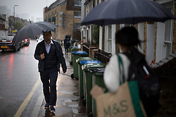 © Licensed to London News Pictures. 27/09/2021. London, UK. Members of the public under umbrellas during a rain shower in Greenwich, South East London. Rain showers are forecasted to continue in parts of London and South East England for the rest of the week.  Photo credit: George Cracknell Wright/LNP