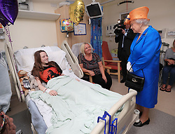 File photo dated 25/05/17 of Queen Elizabeth II speaking to Millie Robson, 15, from Co Durham and her mother, Marie, during a visit to the Royal Manchester Children's Hospital to meet victims of the Manchester Arena terror attack and to thank members of staff who treated them. The NHS will celebrate its 70th anniversary on Thursday 5th July 2018.