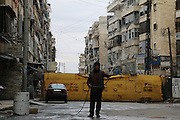 Jan. 5, 2016 - Aleppo, Syria - <br /> <br /> Syrians walk around buses, cars and concrete slabs to protect themselves from the snipers of Syrian regime <br /> <br /> Syrians walk at the street in the northern Syrian city of Aleppo on January 05, 2016. The Syrians used the wreckage buses, cars and concrete slabs to protect themselves from the snipers of Syrian regime forces. <br /> ©Exclusivepix Media
