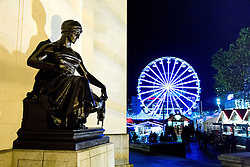 © Licensed to London News Pictures. 29/11/2013. Birmingham, UK. Birmingham Frankfurt Market. Pictured, a statue on the hall of Memory leads the eye to the turning ferris wheel in Milennium Square. Birmingham hosts the largest outdoor Market in the Country every year. The annual Frankfurt German Market, has visited Birmingham for the last 12 years and is bigger than ever before this year. The market has even more stalls, 190 in total. An ice rink and ferris wheel complete the winter wonderland that draws thousands to the city centre over the build up Christmas. Photo credit : Dave Warren/LNP