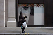 In a scene of youth versus age, a frail and stooping elderly man walks slowly past a young womans face on a poster outside a soon to open Jigsaw shop, on 30th September 2016, at the National Gallery, London, England.