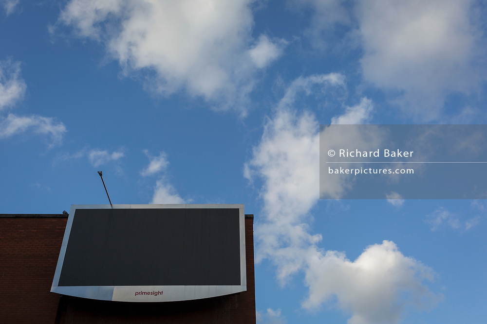 A blank screen of the advertising brand Primesight and clouds in a blue sky, high up on a building on the Walworth Road at Elephant & Castle, on 30th January 2018, in London, England.