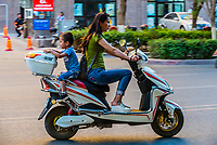 People aboard motorscooters, Turpan, Xinjiang Province, China. Turpan is a small oasis town and former Silk Road outpost. Uyghur people are a Central Asian people of Muslim Turkic origin. They are China's largest minority group.