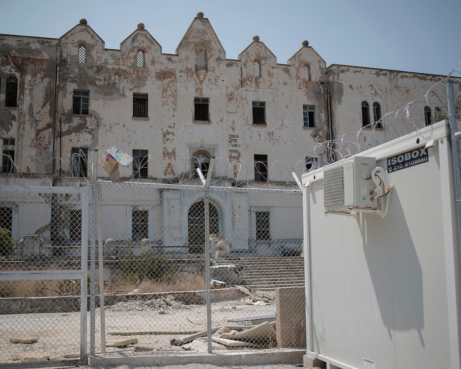 The remains of the abandoned Lepida psychiatric hospital, in whose grounds the Leros 'Hot spot' (an EU-run migrant's reception centre) has been built. <br /> <br /> The Hot Spot in Lepida opened on the 26th of February 2016 in the grounds of the former Lepida psychiatric hospital.  At the beginning it served as a registration camp for refugees and migrants who were travelling to Europe through Greece but since the closure of the borders in March 2016 it serves as a permanent camp. People are allowed to go out, they have three meals a day, the prefabricated huts have a bathroom and are air-conditioned and compering to other refugee camps in Greece the conditions are bearable.
