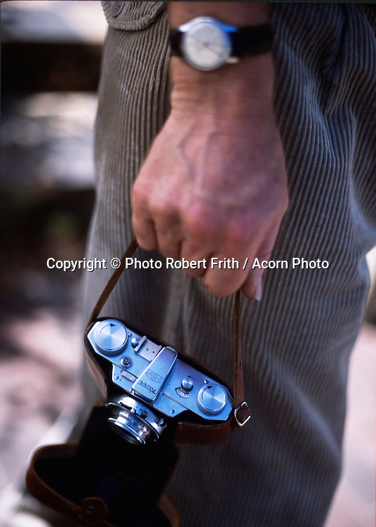 Man's arm holding a vintage film camera and old wrist watch