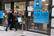 Alongside posters asking customers to observe social distancing, to shop alone and wear a face covering, two shoppers come to within inches of each other while entering and exiting a local Sainsburys supermarket in Mayfair, on 4th March 2021, in London, England.