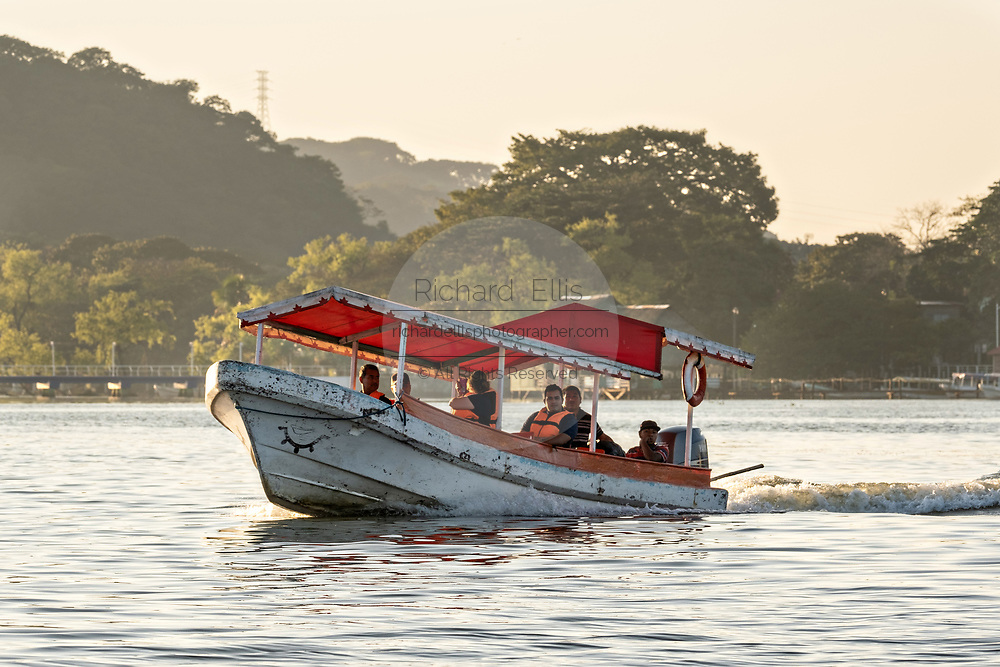 A water taxi called a Panga takes a group of tourists for an evening sightseeing tour around Lake Catemaco in Catemaco, Veracruz, Mexico. The tropical freshwater lake at the center of the Sierra de Los Tuxtlas, is a popular tourist destination and known for free ranging monkeys, the rainforest backdrop and Mexican witches known as Brujos.