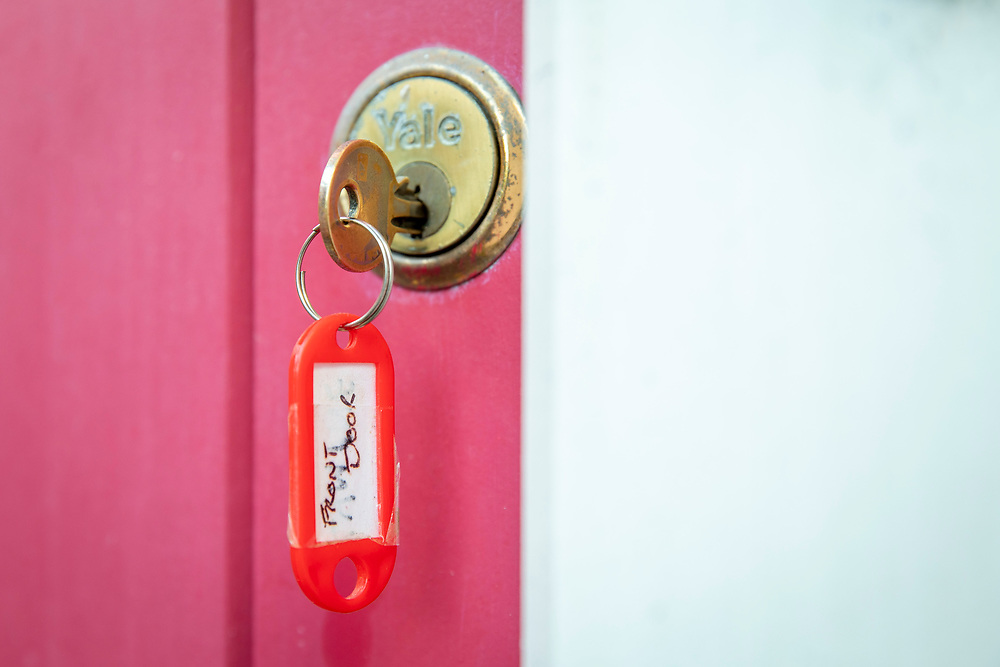 A young woman unlocking her front door using a yeale lock key.