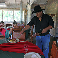 "South America, Brazil, Pantanal. A Pantaneiro serving a barbeque lunch ""cowboy style"" at the Cordilheira Lodge of the Caiman Ecological Reserve."
