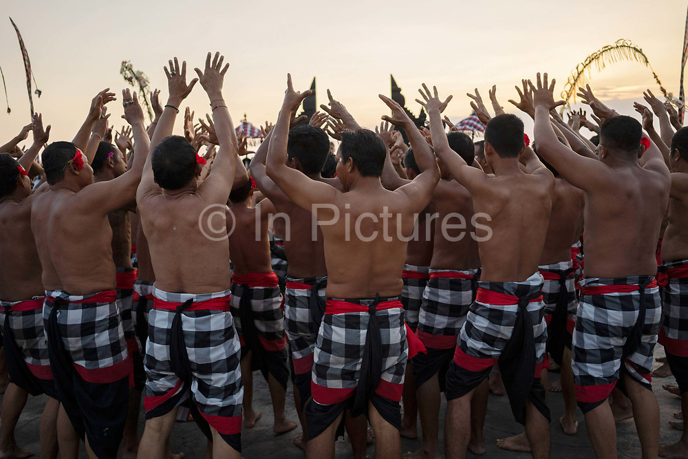 Male dancers wearing traditional costumes participate in the Kecak fire dance, which takes place at the Pura Luhur Uluwatu Temple at the southernmost tip of the island on 17th June, 2018 in Bali, Indonesia. It is a sacredly positioned temple, believed to protect the island from evil spirits, and the fire dance performance is an adaptation of the Ramayana Hindu story.