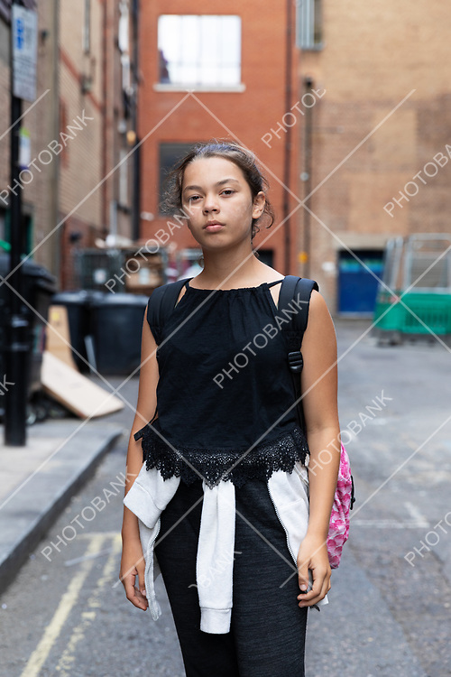Portrait of a young girl in an alley full of garbage. Casual clothes. Urban context