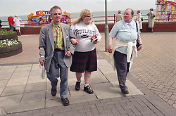 Group of people with learning disabilities walking along seaside pier,
