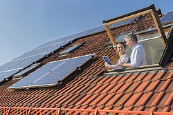 Couple holding digital tablet and looking out from roof window with solar panels