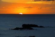 The sun sets over Waimea Bay.