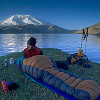 CHINA, Xinjiang Province. Mark Newcomb<br /> (MR) wakes from bivouac by Lake Karakul in Pamir Mountains. 7546m Mustagh Ata bkg.