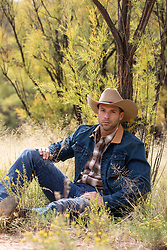 cowboy relaxing on a Fall day under a tree in a field