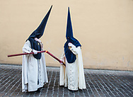 Nazarenos helping each other in keeping the flame of candles burning. Cordoba, Spain.