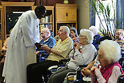 Rev. Paula Maina Waithaka greets residents at The Abbington of Glenview healthcare residence after celebrating a mass on Wednesday, August 20th. Waithaka is Pastor at St. Catherine Laboure in Glenview. August 20th, 2014 l Brian J. Morowczynski-ViaPhotos<br /> <br /> For use in a single edition of Catholic New World Publications, Archdiocese of Chicago. Further use and/or distribution may be negotiated separately. <br /> <br /> Contact ViaPhotos at 708-602-0449 or email brian@viaphotos.com.