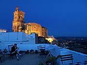 A traveler reads atop La Casa Grande, a small bed and breakfast inn in Arcos de la Frontera. The church of Saint Peter ? one of the city's two most prominent churches ? can be seen in the near distance, hugging the edge of Arcos' famous cliffs.