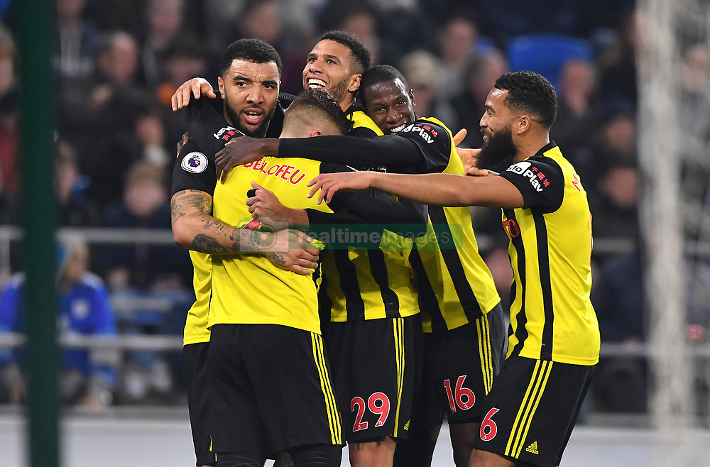 Watford's Gerard Deulofeu (left) celebrates scoring his side's third goal of the game with team-mates during the Premier League match at the Cardiff City Stadium.