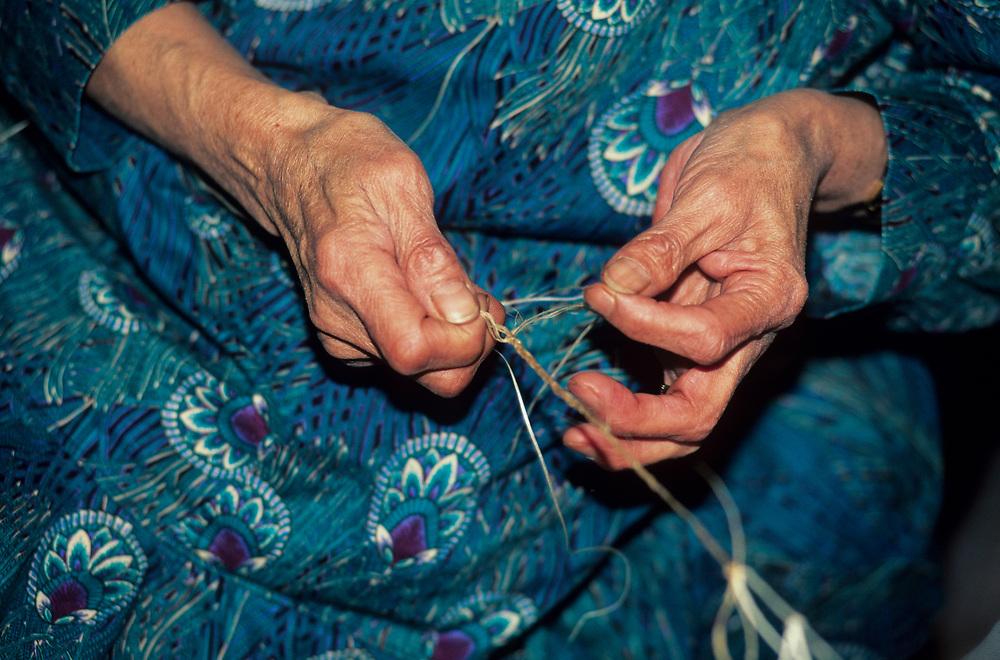 Alaska. Barrow. Elder native tying caribou sinew.
