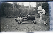 young child playing outdoors with dog 1920s
