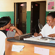 INDIVIDUAL(S) PHOTOGRAPHED: Jenifer (left) and Siyanbade Mojisola (right). LOCATION: Onigbongbo Health Care Center, Lagos, Nigeria. CAPTION: Siyanbade Mojisola writes down her patient Jenifer's blood pressure during an examination.