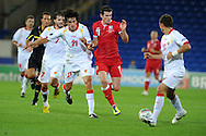 Gareth Bale of Wales (r) is challenged by Stefan Savic (21). Euro 2012 Qualifying match, Wales v Montenegro at the Cardiff City Stadium in Cardiff  on Friday 2nd Sept 2011. Pic By  Andrew Orchard, Andrew Orchard sports photography,