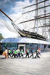 A group of school children walking past the Cutty Sark in Greenwich.