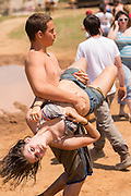 A young is dragged off by her boyfriend during the 2015 National Red Neck Championships May 2, 2015 in Augusta, Georgia. Hundreds of people joined in a day of country sport and activities.