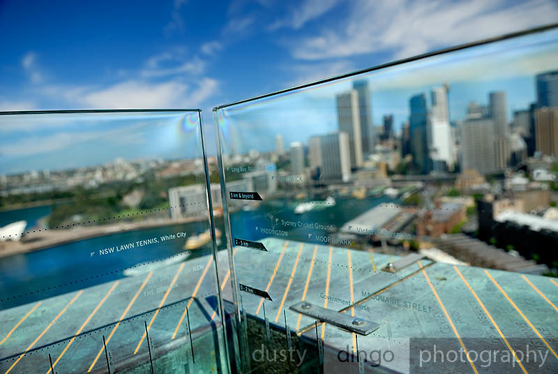 The names of places of interest are etched into a glass panel around the 87 metre high Sydney Harbour Bridge Pylon Lookout. Arrows engraved into copper cladding point out those locations. In this view, Circular Quay and the Sydney skyline are in the background. Sydney, Australia