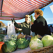 A couple buy vegetables at a Christmas market in the picturesque village of Hovingham in North Yorkshire, UK.