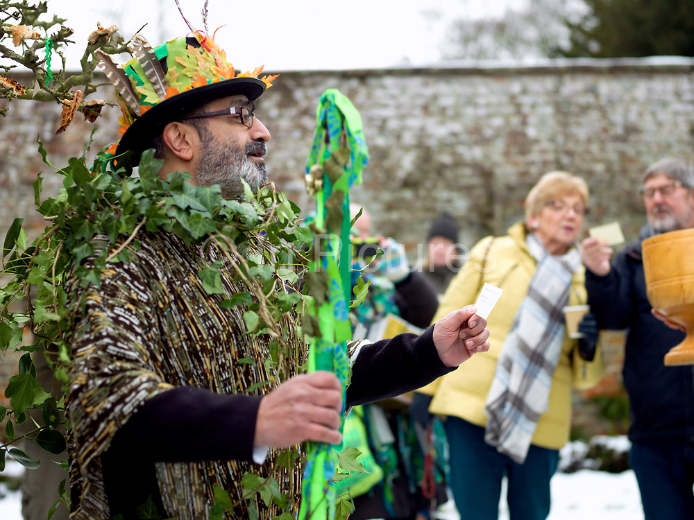 The Green Man at an orchard-visiting wassail at Sledmere House, Yorkshire Wolds, UK on 20th January 2018. Wassail is a traditional Pagan winter celebration in cider-producing regions of England, reciting incantations and singing to the trees to promote a good harvest for the coming year. Pieces of toast soaked in cider are hung in the branches to attract robins to the tree as these are said to be the good spirits of the orchard. To ward off evil spirits, villagers scare them away by banging pots and pans and making as much noise as possible