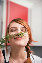 Woman smelling a twig of rosemary, Munich, Bavaria, Germany