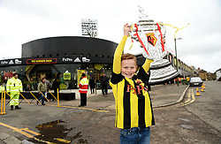 A young Watford fan holds a hand made trophy ahead of the match