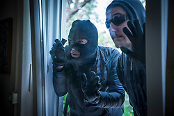 Two burglars peeking through glass door of house