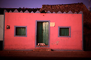MEXICO, YUCATAN PENINSULA a brightly painted village house with sleeping dog near Chichen Itza