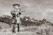Mountain Man in front of the Grand Teton mountain range in northwest Wyoming. The hunter is setting traps and hunting along the streams and creeks.