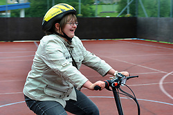Woman with learning disabilities has a go at riding a tricycle; as part of a Sport Ability Day North Yorkshire, UK