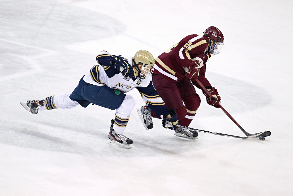 Boston College forward Paul Carey (#22) skates with the puck while Notre Dame right wing Billy Maday (#17) backchecks in second period action of NCAA hockey game between Notre Dame and Boston College.  The Notre Dame Fighting Irish defeated the Boston College Eagles 3-2 in game at the Compton Family Ice Arena in South Bend, Indiana.