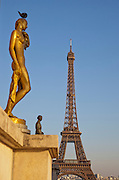 Golden statues at the Palais de Chaillot at the Trocadero before the iconic Eiffel Tower in Paris, France