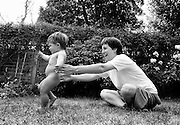 """""""Homo erectus."""" At the exact moment that a young human being walks for the first time, an eleven month-old girl infant conquers her fear and takes her first tentative upright unaided steps. After months of building lower leg strength by pushing and leaning against household objects, she now leaves the protective hands of a delighted but nervous mother who relishes the joyous moment of her offspring's great achievement. The girl's legs and hips help propel her forward motion, naturally making her an upright bi-pedal species. This is from a documentary series of pictures about the first year of the photographer's first child Ella. Accompanied by personal reflections and references from various nursery rhymes, this work describes his wife Lynda's journey from expectant to actual motherhood and for Ella - from new-born to one year-old."""