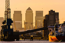 North Woolwich, London, October 28th 2014. A ship prepares to leave the Tate and Lyle sugar factory as the late afternoon sun silhouettes Docklands.