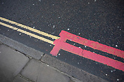 Red and yellow double lines in the City of London on 5th February 2020 in London, England, United Kingdom. A double yellow line is a painted marking separating two lanes of a road. It consists of two parallel, solid yellow lines, and its presence usually indicates a no-passing restriction or no passing zone, where crossing the line is prohibited. Red routes are marked with red lines at the sides of the road. Double red lines mean that the regulations apply at all times and on all days, including no stopping. Single red lines means that the prohibition applies during times displayed on nearby signs or at the entry to the zone.