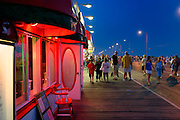 Vacationers strolling along the boardwalk at night.