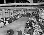"""Y-480418-04. Celilo Village longhouse, Feast of the First Salmon dinner. April 18, 1948. Standing in rear, Chief Tommy Thompson and Henry Charlie. The purpose of this annual feast was to give thanks and welcome the first salmon to start the spring run up the Columbia River. With the beginning of each year's new salmon run, Celilo Indians could eat fresh fish instead of the dried salmon they preserved from the year before. Historically this was expected to be the second or third week of April, but the Indians would begin the celebration only after the fish actually appeared. Just the year before, in 1948, Chief Tommy Thompson had gone to the Warm Springs reservation to invite all the Indians to Celilo for the feast on the next  weekend when the fish were anticapated, but when the fish didn't run he had to postpone the ceremony for another week. And nine years before, in 1940, the feast was held on the first weekend of April, at the time it was said to be the earliest the feast had ever been held. Attendance had ranged from, according to newspaper reports, 47 Indians in 1938, rising to 600 at this one. The following year, in 1949, the feast was again postponed due to no fish. With the end of Celilo in the forseeable future, crowds continued to grow and finally, in 1956, at the last Feast of the First Salmon before the innundation, unseasonably warm weather in the late winter thawed the ice fields and Celilo falls flooded making fishing impossible. Celilo Indians were forced to buy 400 pounds of salmon on the commercial market in Portland to feed the crowd, which the newspaper reported as being comprised of """"More white folks with cameras than Indian fishermen with dipnets."""" Ever since the falls were covered, the feast has been held at a pre-arranged time."""