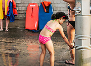 Young girl washes off sand in a public beach shower, Nauset Beach, Cape Cod, Massachusetts, USA