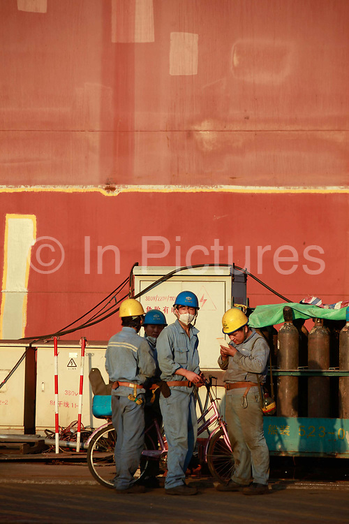 Workers stand by a ship under construction at the China State Shipbuilding Corp.'s (CSSC) Longxue Shipyard in Guangzhou, Guangdong Province, China, on Sunday, Nov. 13, 2011. China is the world's biggest shipbuilder, however recent economic downturns have caused a glut in supplies.