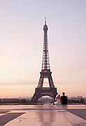 A newly married couple sit at the Trocadero before the Eiffel Tower in Paris, France